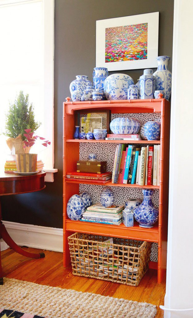 Coral faux bamboo bookshelf and blue and white china pottery via Aunt Peaches