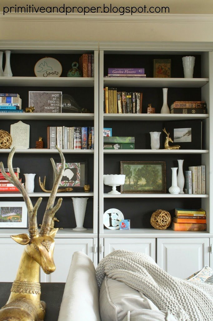 Brass animals on black backed bookcases via Primitive and Proper