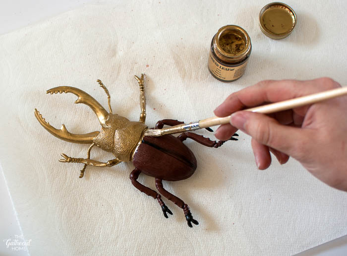 Paint plastic insects with liquid gold leaf
