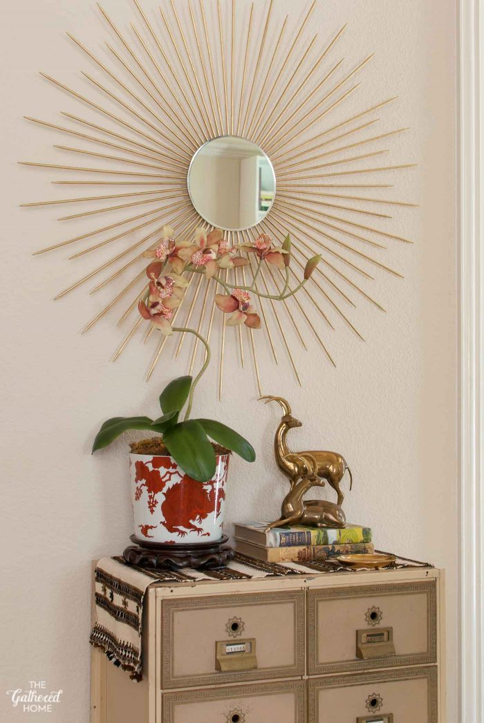 """Entryway vignette: vintage Fitz & Floyd """"temple dragon"""" planter, silk orchids, brass antelope and vintage post office box."""