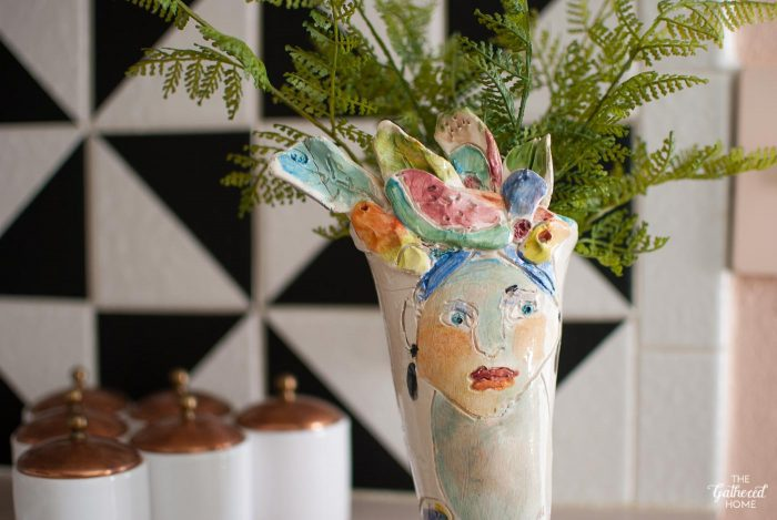 This perfectly imperfect handmade pottery woman with a fruit hat vase was found at a thrift store.