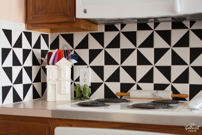 This patterned kitchen backsplash makeover has the look of trendy and expensive cement tiles but (1) didn't involve painting the existing tiles, (2) is SUPER affordable, and (3) can be completed in one afternoon!