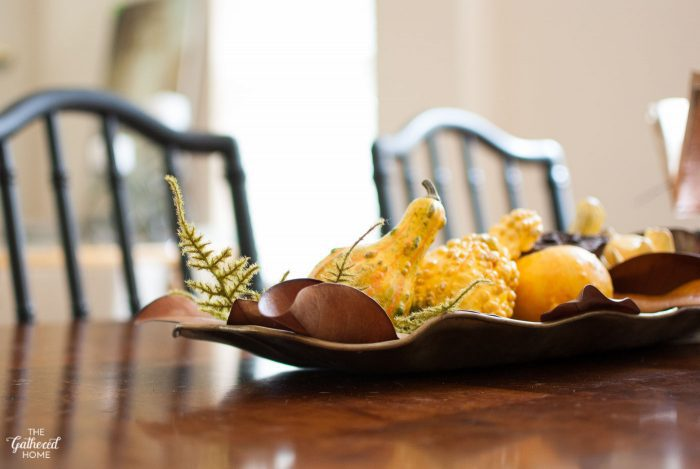 Celebrate sculptural gourds by displaying them in a brass tray with fall ferns and leaves.