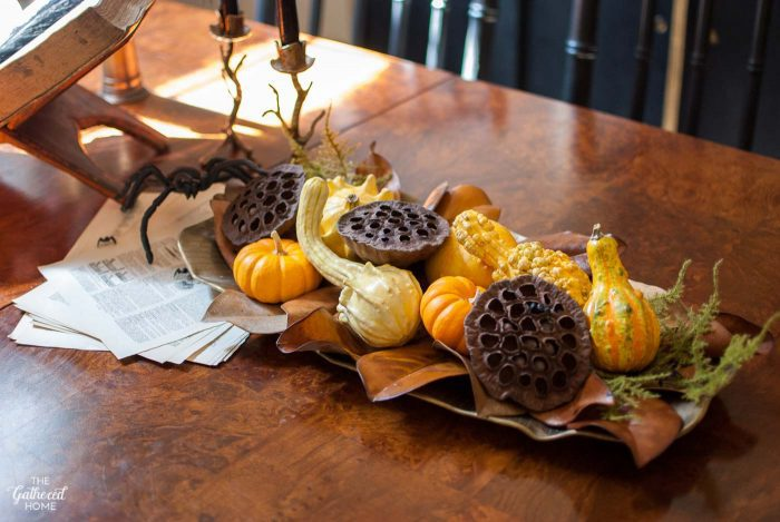 Fill a brass tray with creepy yet beautiful offerings from nature: warty gourds, dried lotus pods, shriveled leaves, and, of course: spiders.