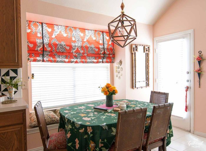 This built-in window seat eating nook got a fun makeover with pink walls and bold faux Roman shade window treatment.