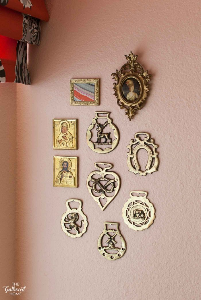 Mini gallery wall made of thrifted brass horse medals and gold frames on pink kitchen walls