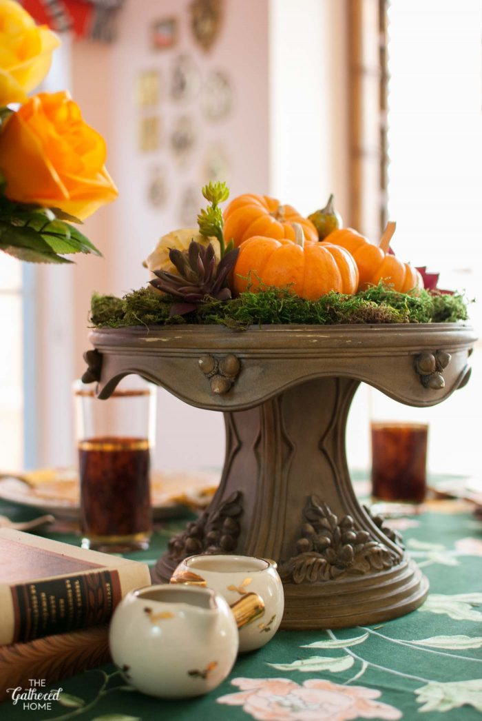 Whip up a simple Thanksgiving table centerpiece in no time with sheet moss, pumpkins, and faux succulents on a pretty cake stand.