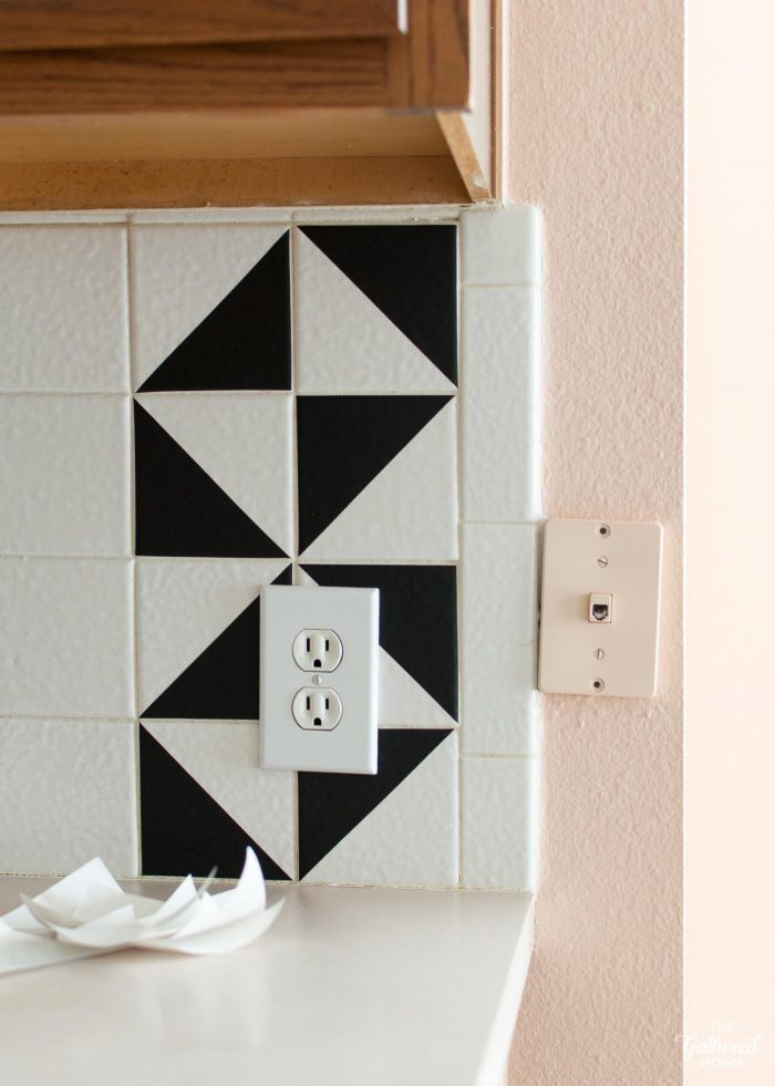 DIY black vinyl triangles on tile backsplash