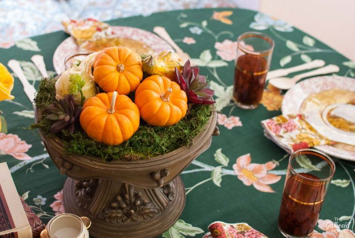 Pumpkin, moss, and faux succulents make a beautiful Thanksgiving table centerpiece when displayed on a lovely cake stand!