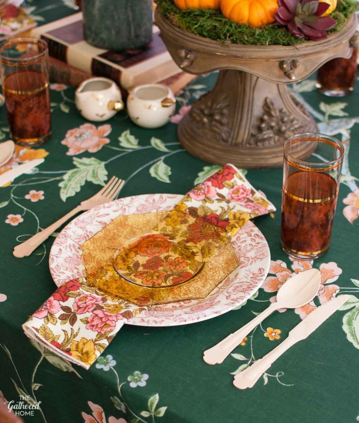 A Thanksgiving table setting with mixed floral patterns, vintage glassware, and birchwood cutlery.