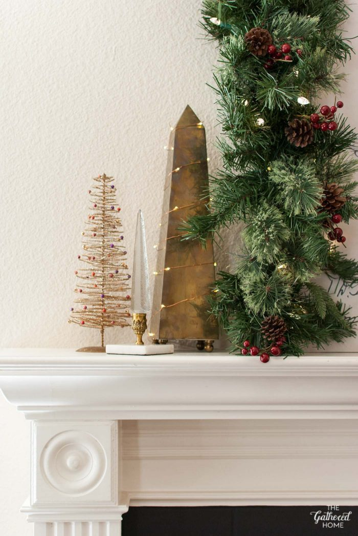 "Fairy lights help this vintage brass obelisk fit perfectly into this trio of found ""Christmas trees"""