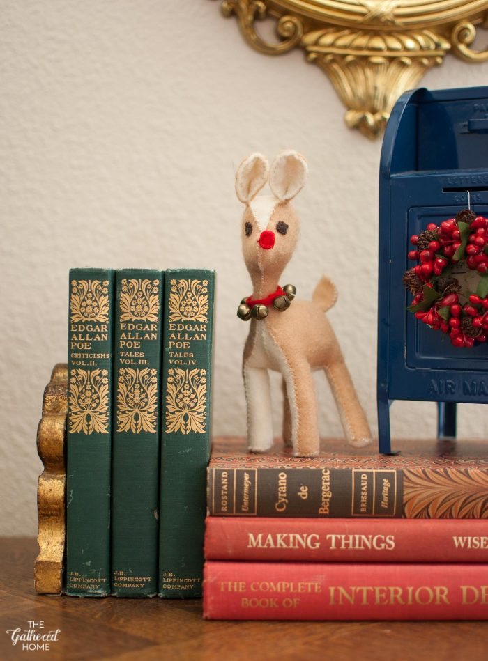 A handmade felt Rudolph figurine on a pedestal of vintage Christmas-colored books
