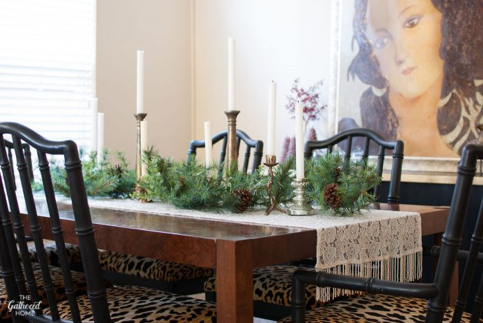 Winter wonderland Christmas dining room table. A thrifted beaded wrap functions as a table runner - then add garland, mis-matched candlesticks, pinecones, and white candles to finish it up!