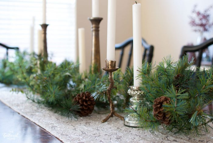 Mismatched thrifted candlesticks create this eclectic Christmas table centerpiece.