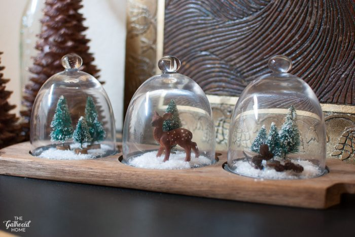"Tiny bottlebrush trees, a mini toy fawn, itty bitty pine cones, and sparkling fake snow are all it takes to create these adorable little ""snow globe"" displays!"