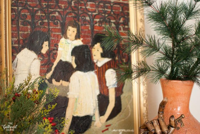 Faux pine greenery brings out the holiday colors in this thrifted oil painting