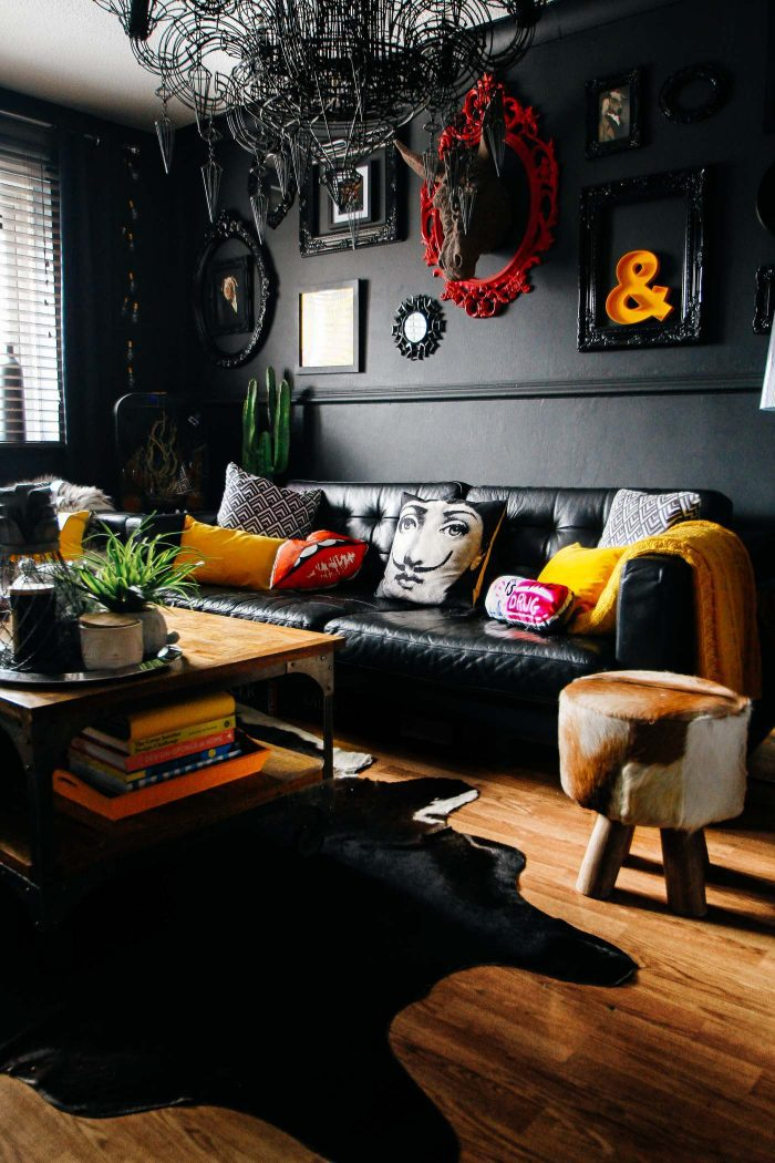 Black sofa on black walls, with colorful accessories and a whimsical wireframe chandelier in this gathered home tour