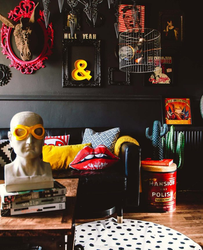 Black walls provide a striking background for the playful and colorful accessories in this gathered home in the UK