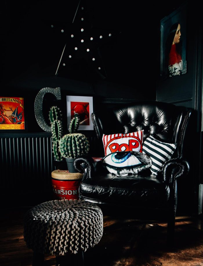 Black leather wingback plus bold pop pillows, via a stunning gathered home in the UK