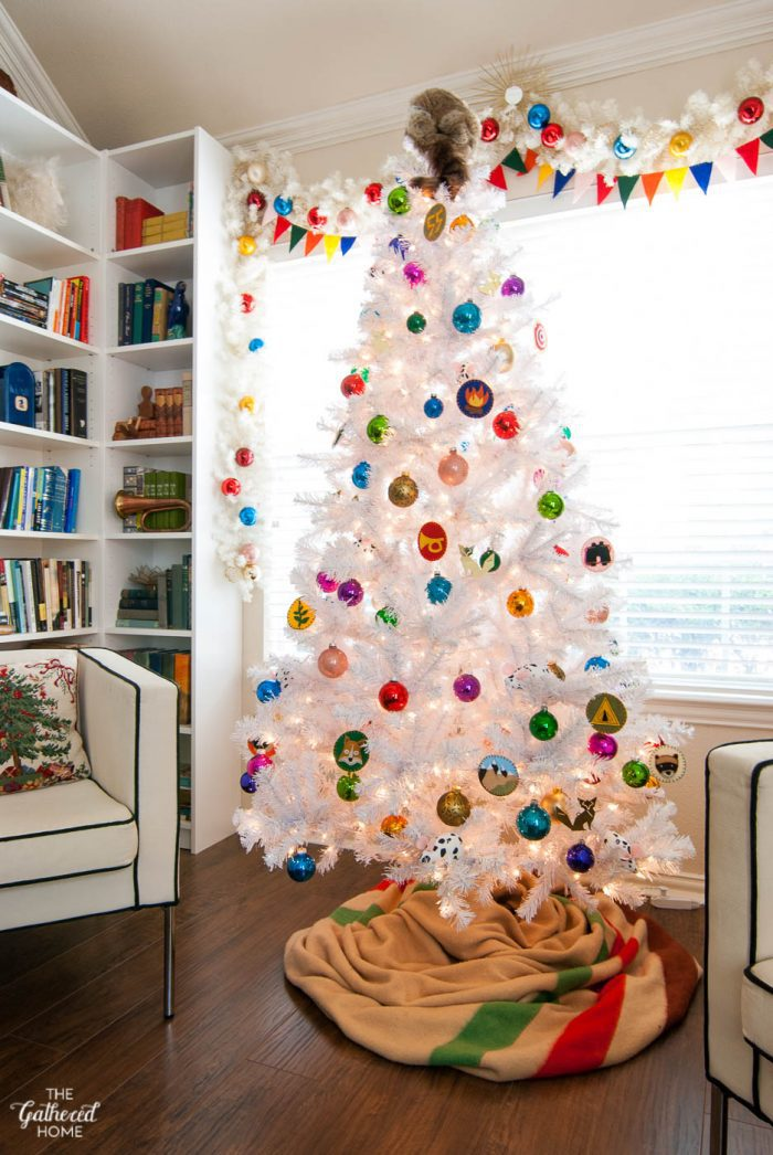 White Christmas tree with colorful glass ornaments and a vintage scout camping theme inspired by Wes Anderson's Moonrise Kingdom.